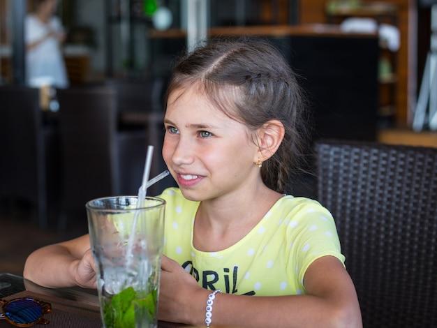 美しい少女はカクテルを飲んでいます。