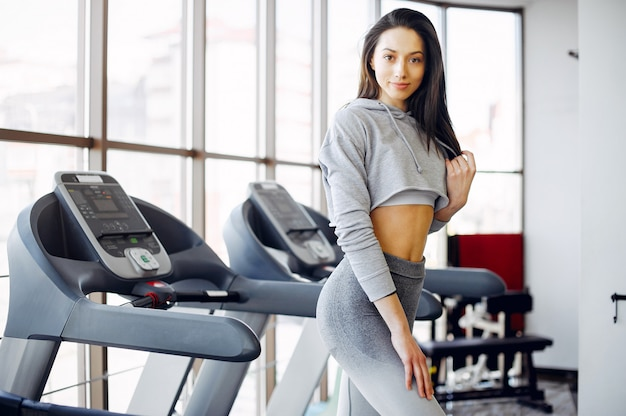 Beautiful girl is engaged in gym