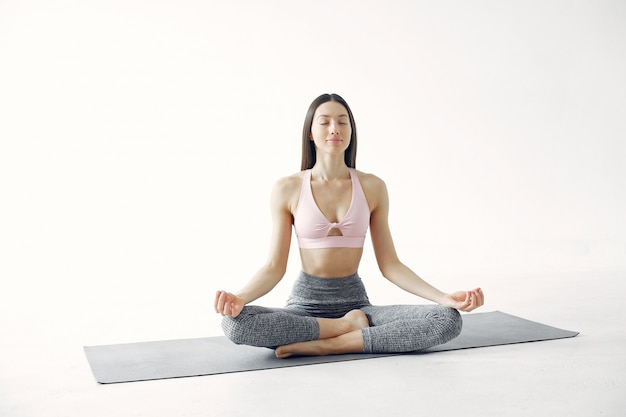 A beautiful girl is engaged in a yoga studio