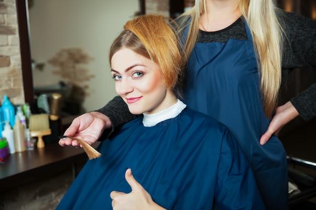 아름다운 소녀는 선택한 머리 색깔에 만족합니다.