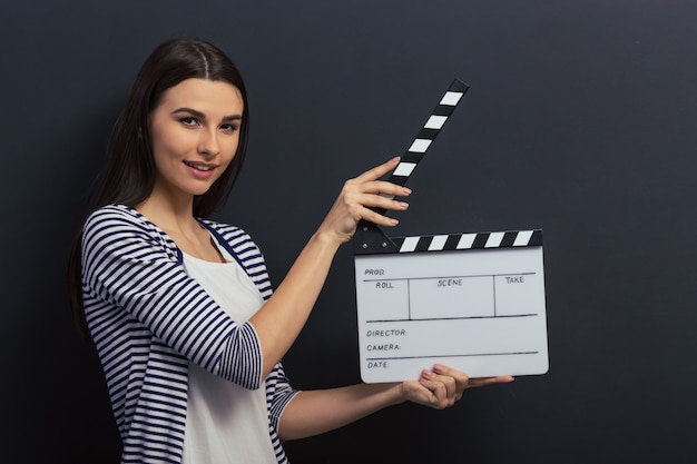 Beautiful girl is holding a clapperboard, looking at camera.