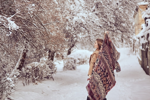 Beautiful girl is holding fluttering scarf in a winter park
