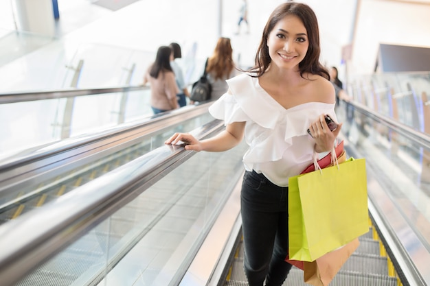 Beautiful girl is holding shopping bags and smiling while doing shopping in the supermarket/mall