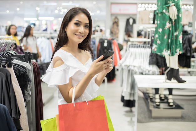 Beautiful girl is holding shopping bags and using a smart phone and smiling while doing shopping