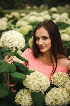 Красивая девушка находится в кустах цветов гортензии в саду заката. на улицах города распускаются цветы.