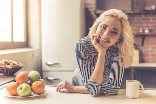 Beautiful girl is leaning on table near the plate of fruits