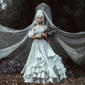 美しい少女は中世の歴史的なドレスでポーズをとってください。