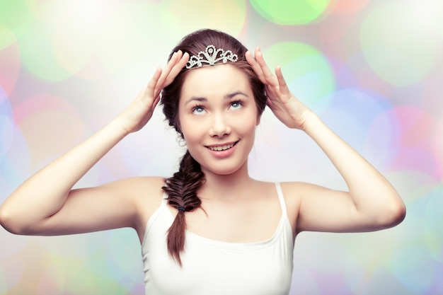 Beautiful girl is putting on a diamond diadem and admiring it