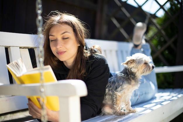 晴れた日に犬と一緒にベンチに横たわっている美しい少女が本を読んでいます。庭のコンセプトで休息とリラックス。屋外レクリエーション。村の休日。暖かい晴れた夏の日。
