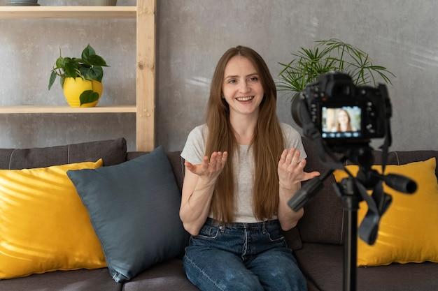 아름다운 소녀가 비디오 블로그에 무언가를 기록하고 있습니다. 젊은 블로거가 직접 말하고 영화를 촬영합니다. . 인기있는 취미