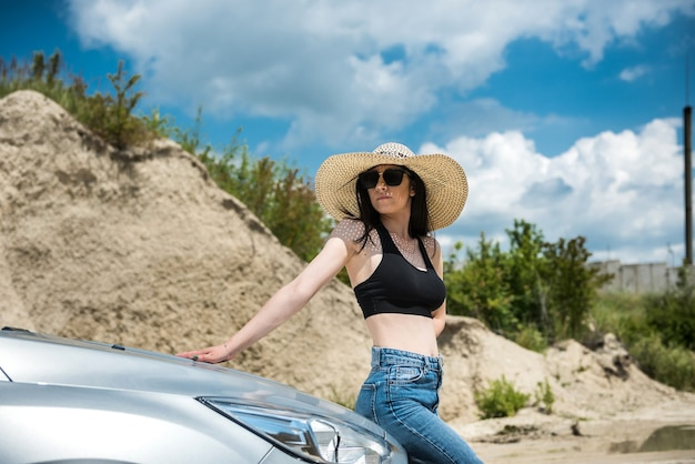Beautiful girl is resting outside the city and posing near the car