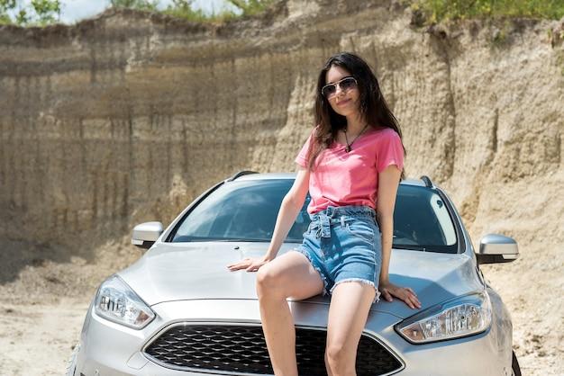 아름다운 소녀는 도시 밖에서 쉬고 차 근처에서 포즈를 취하고 있습니다.