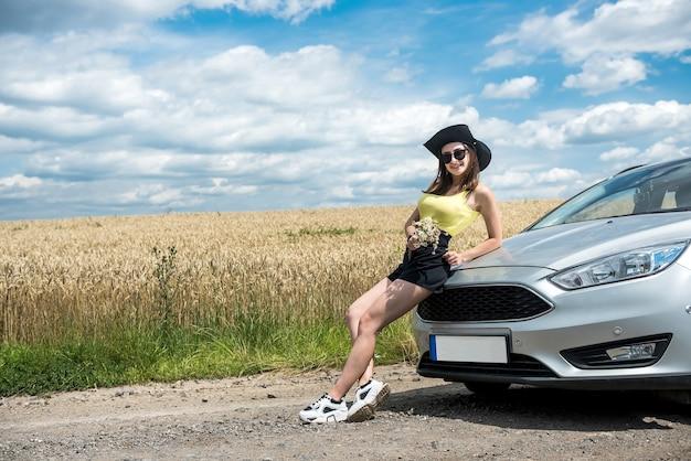 아름다운 소녀가 도시 밖에서 쉬고 차 근처에서 포즈를 취하고 있다