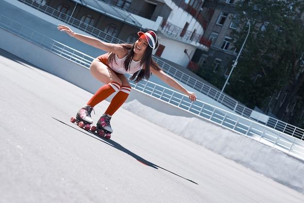 Красивая девушка катается на роликах в скейт-парке, она делает это очень активно
