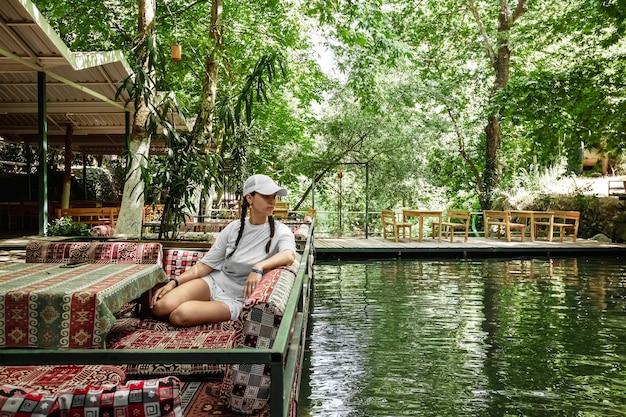 Красивая девушка сидит в ресторане на природе. ноутбук, отдых.