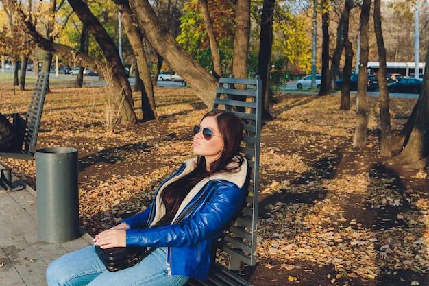 A beautiful girl is sitting on a park bench on a background of green nature.