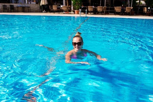 美しい少女がプールで泳いでいます