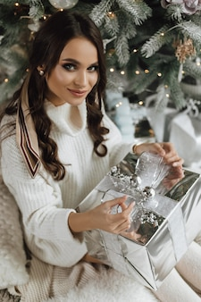 Beautiful girl is unpacking a gift in silver paper and tape
