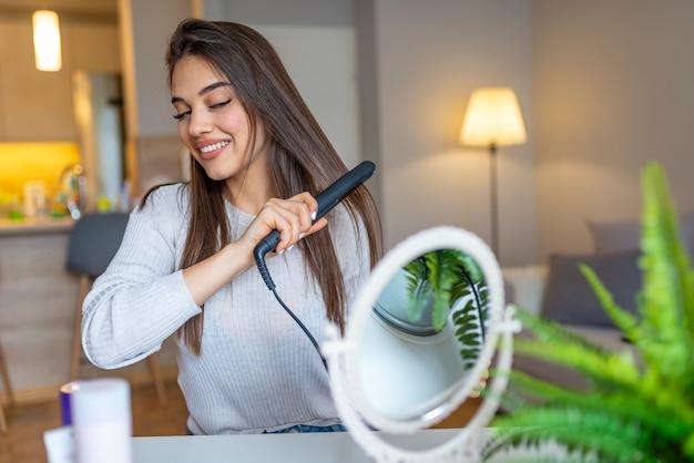 Красивая девушка использует выпрямитель для волос и улыбается, глядя в зеркало на дому. усмехаясь женщина выправляя волосы с раскручивателем волос дома.