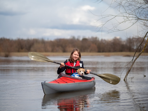 A beautiful girl and a jack russell terrier puppy are traveling on a red kayak .