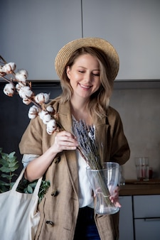 Beautiful girl in jacket with tote bag and cotton-plant in a kitchen at home. healthy and ecology concept of lifestyle