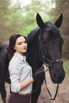 Красивая девушка жокей райдер с черной лошади, одетые в легкую рубашку в зеленом форест парк.