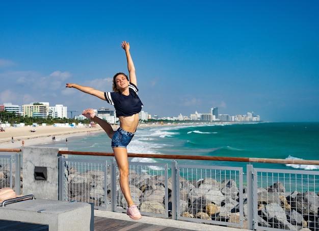 美しい少女は、マイアミビーチを背景にサウスビーチでジャンプします。フロリダ。幸福と自由の概念。