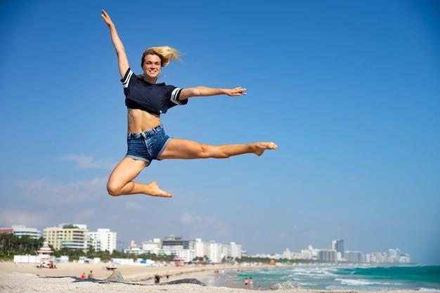 아름 다운 소녀 배경, 마이애미 비치에 사우스 비치와 점프. 플로리다. 행복과 자유의 개념. 프리미엄 사진