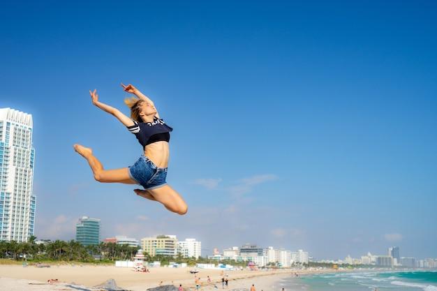 Красивая девушка прыгает с южного пляжа на фоне майами-бич. флорида. понятие счастья и свободы.