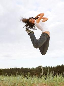 Красивая девушка прыгает в парке
