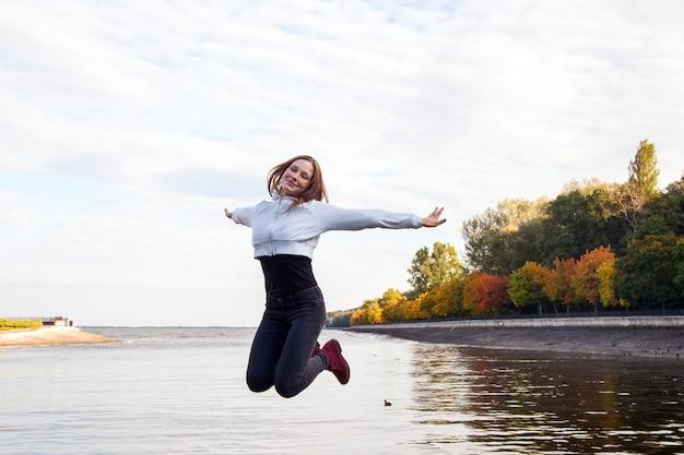 湖の近くの公園の道をジャンプする美しい少女。幸せとかわいい若い大人のモデル。アウトドアショット