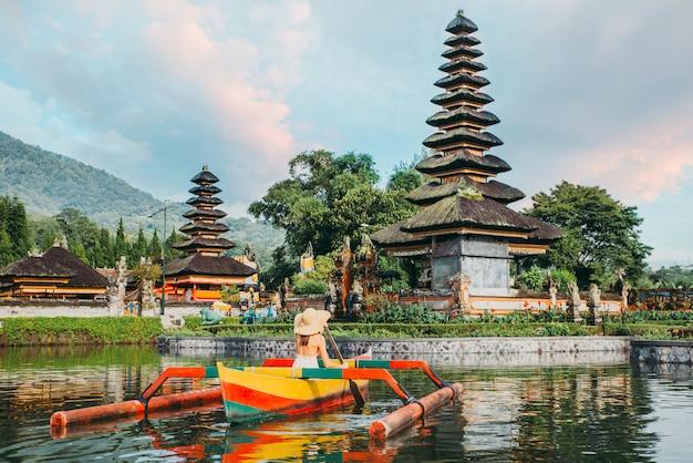 Beautiful girl kayaking on the catamaran at the ulun datu pura bratan temple, in bali