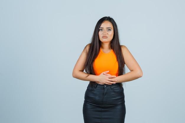 Красивая девушка держит руки на животе в оранжевом топе и юбке и выглядит болезненно, вид спереди.