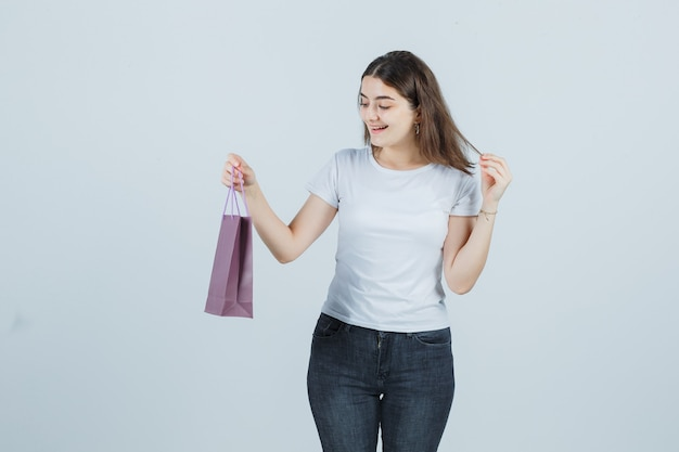 Beautiful girl keeping papper bag in t-shirt, jeans and looking happy . front view.