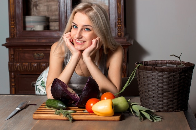 Beautiful girl in the kitchen wearing an apron with chopped vegetables on a board