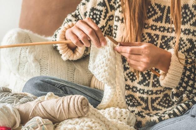 美しい少女はベッドに暖かいセーターを編んでいます。趣味の編み物。編み物用アクセサリー。