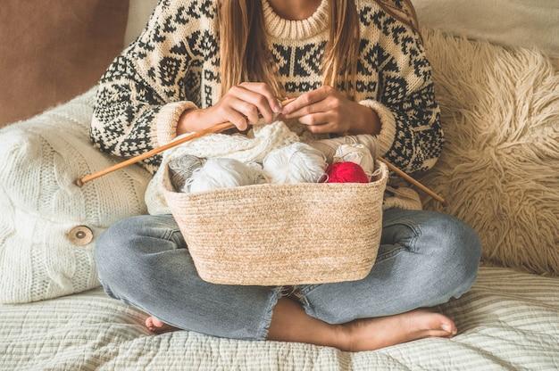 Красивая девушка вяжет на кровати теплый свитер. вязание для души. аксессуары для вязания.