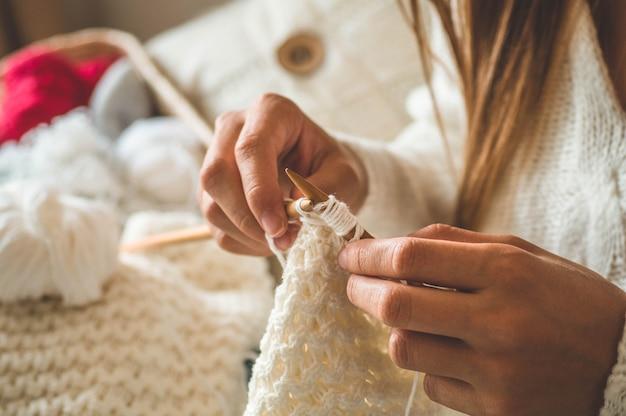 Красивая девушка вяжет теплый свитер