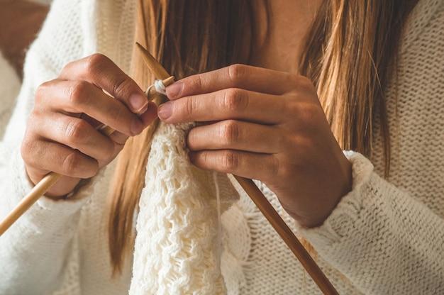Beautiful girl knits a warm sweater