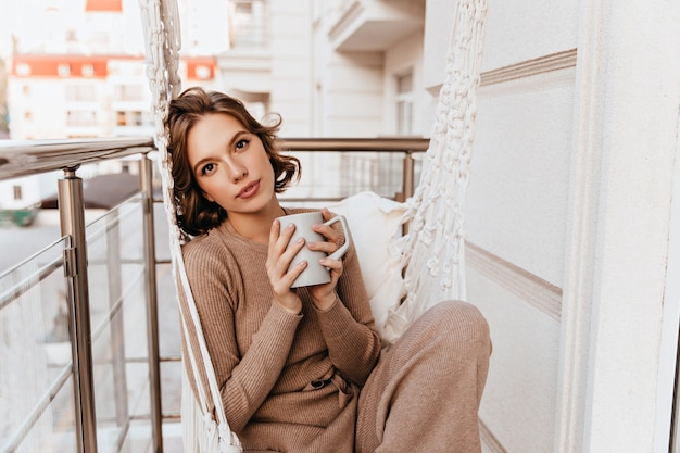 Beautiful girl in knitted dress drinking coffee in morning. romantic caucasian young woman holding cup of tea at balcony.