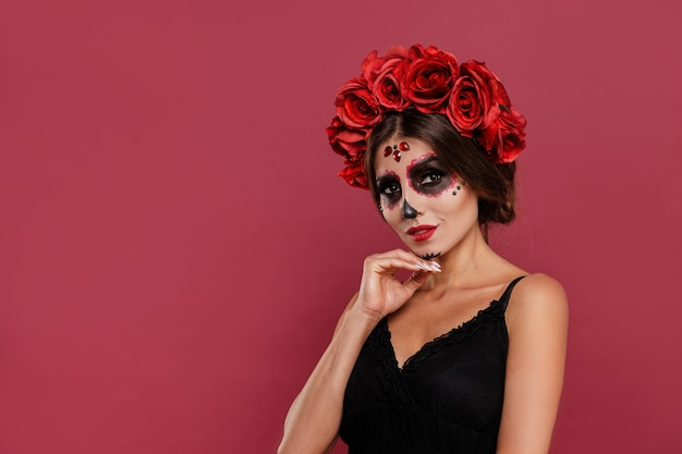 Beautiful girl in la muerta attire and skull make up looking to camera during halloween