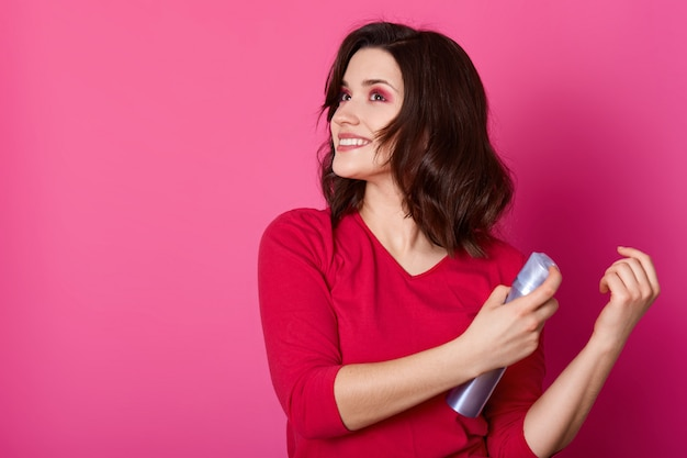 Beautiful girl laying fixes using hairspray, prepares for dating with boy friend, makes new hairstyle. smilling brunette poses isolated on pink wall, looks aside, holds bottle of moussein hands.