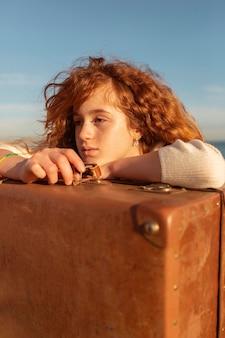 スーツケースのクローズアップに横たわっている美しい少女