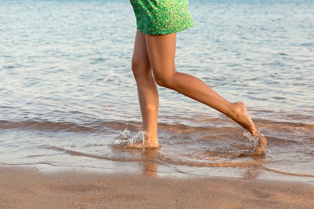 Beautiful girl legs running on the beach. pretty girl walking on water