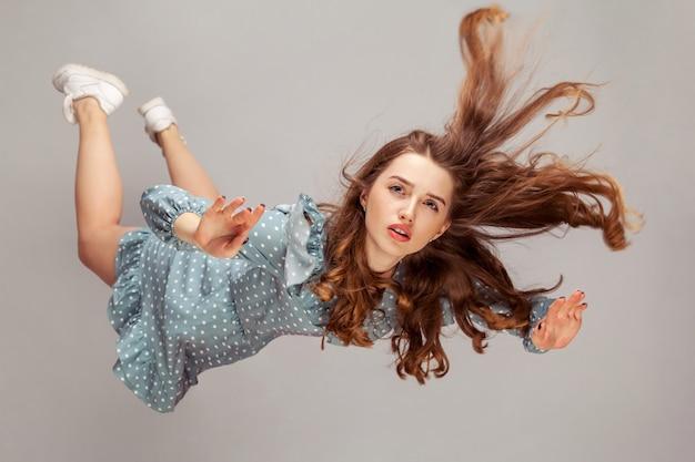 Красивая девушка парит в воздухе, падает, и ее волосы спутаны, взлетая от ветра