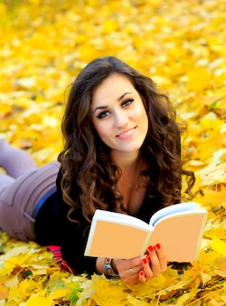 Beautiful girl lies on yellow leaves and reading a book
