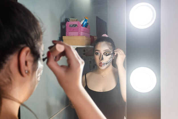 Beautiful girl lifting her eyelashes, halloween makeup done in her room.