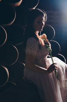 Beautiful girl in a light dress with bouquet of flowers among metal pipes