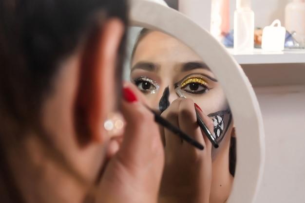 Beautiful girl lining her eyes with halloween makeup in her bedroom.