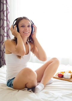 Beautiful  girl listening to music on headphones in bed